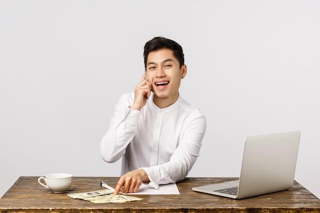 Sucesso, riqueza e conceito corporativo. feliz e rico jovem empresário masculino asiático no escritório, contando dinheiro, dólares na mesa, sentado e rindo como smartphone falando, chamando de parceiros de negócios