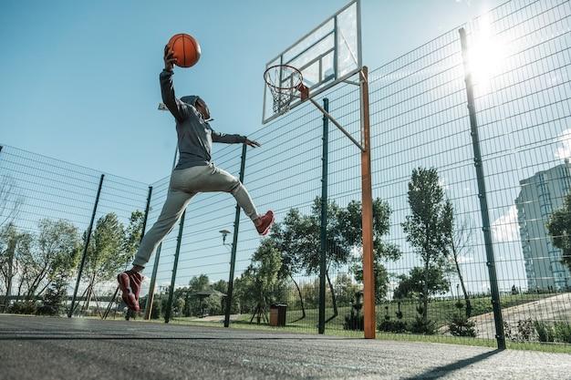 Sucesso verdadeiro. homem bom e forte pulando enquanto joga a bola