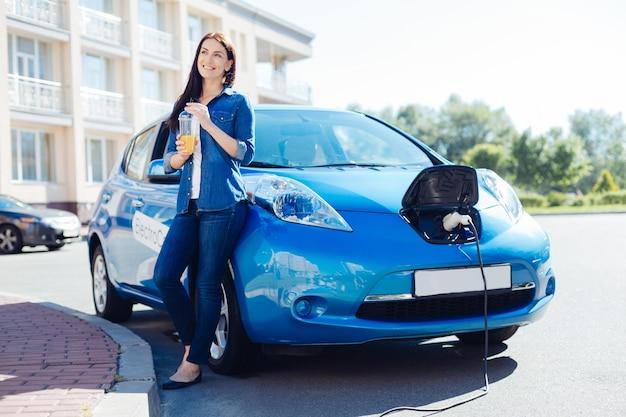 Suco acabado de fazer. mulher feliz encantada e simpática encostada em seu carro elétrico e sorrindo enquanto saboreia seu suco de laranja feito na hora