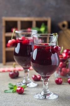 Suco caseiro de cereja fresca em um copo com frutas frescas em estilo rústico.