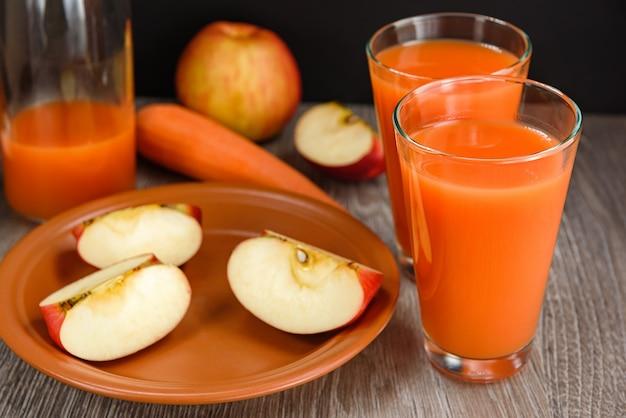 Suco, cenoura e fatias de maçãs no prato