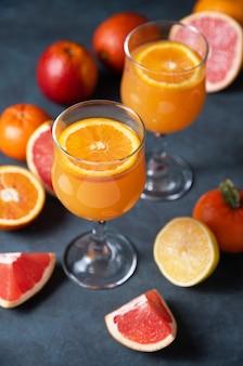 Suco cítrico em dois copos e frutas frescas, tangerina, laranja, toranja e limão em um fundo cinza escuro. vista do topo