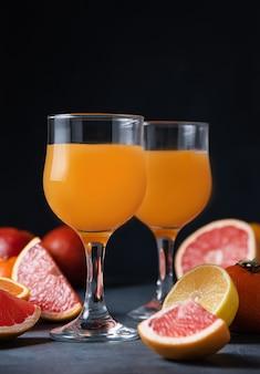 Suco cítrico em dois copos e tangerina de frutas frescas, laranja, toranja e limão em um fundo preto. vista frontal