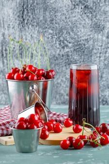 Suco com cerejas, tábua, toalha de cozinha em uma jarra, vista lateral.