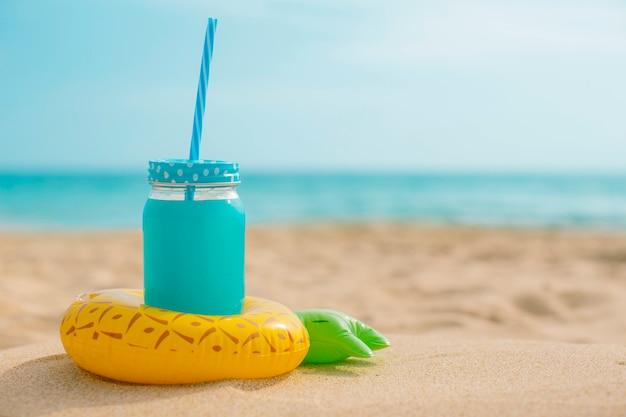 Suco de abacaxi com um inflável na praia