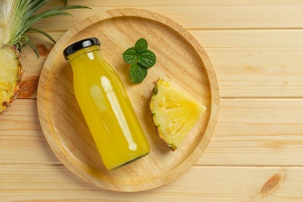 Suco de abacaxi em garrafa na superfície de madeira