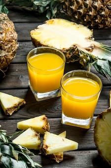 Suco de abacaxi em um copo e fatias de abacaxi fresco. em fundo de madeira