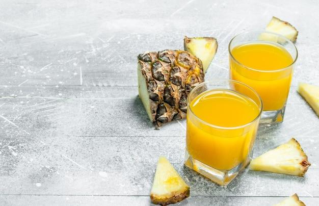 Suco de abacaxi em um copo e fatias de abacaxi perfumado. em fundo rústico
