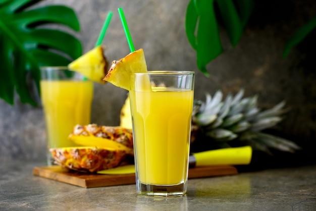 Suco de abacaxi espremido na hora em dois copos colocados sobre a superfície de uma mesa de bar de mármore escuro