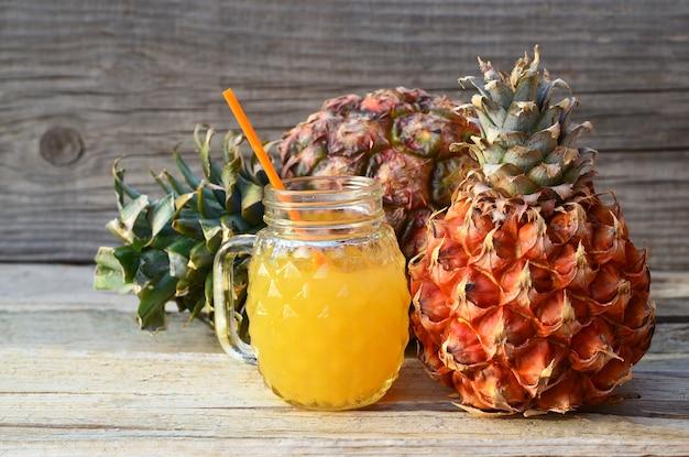 Suco de abacaxi espremido na hora em um copo de vidro com canudo e frutos maduros de ananás na mesa de madeira velha.