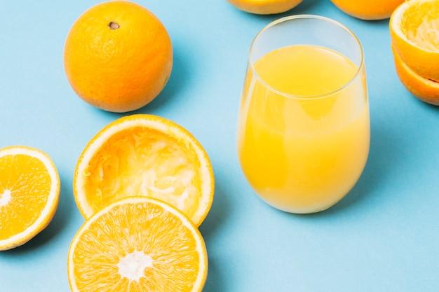 Suco de alto ângulo feito de laranjas em vidro