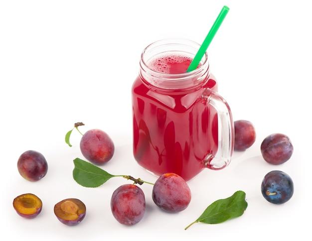 Suco de ameixa em um copo com frutas frescas de ameixa, isolado no fundo branco.