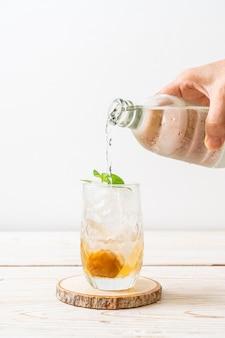 Suco de ameixa gelado com refrigerante e hortelã-pimenta na mesa de madeira. bebida refrescante