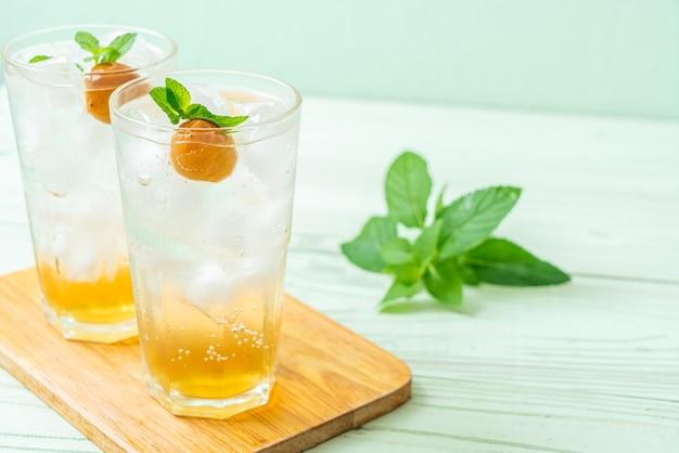 Suco de ameixa gelado com refrigerante e hortelã-pimenta na mesa de madeira - bebida refrescante