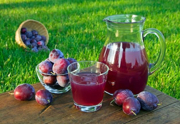 Suco de ameixa na jarra e copo com fundo natural de ameixas em dia de sol