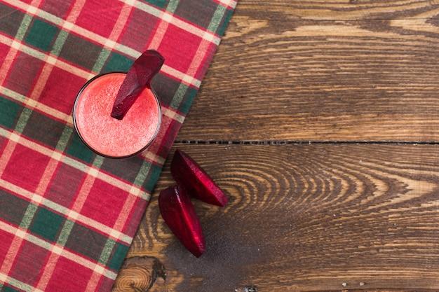 Suco de beterraba em um copo em uma mesa de madeira