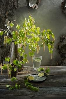 Suco de bétula com fatias de limão, ramos jovens e botões floridos de bétula. cozinha russa