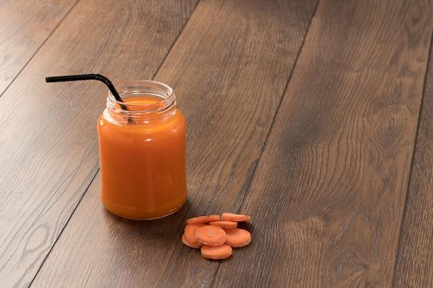 Suco de cenoura em um copo de madeira