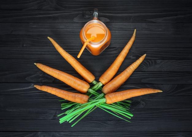 Suco de cenoura em uma jarra de vidro com cenouras frescas