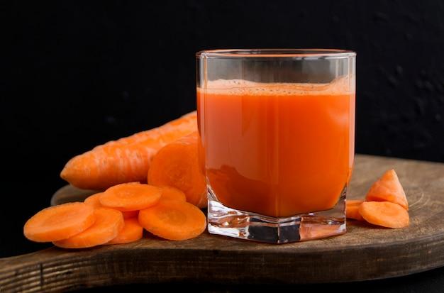 Suco de cenoura espremido na hora em fundo preto
