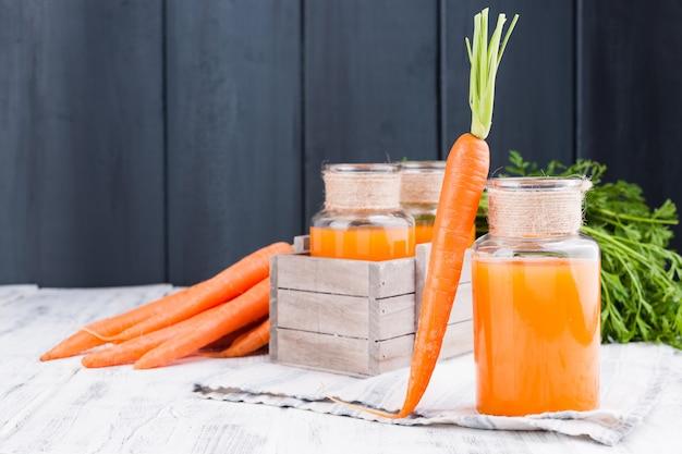 Suco de cenoura fresco em uma jarra. cenouras frescas com folhas e bebida. comida de primavera para saúde e beleza