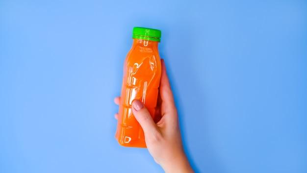Suco de cenoura nas mãos.