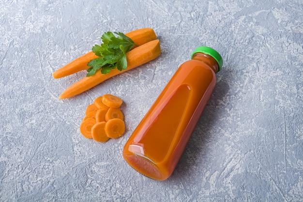 Suco de cenoura nutritivo detox em frasco de vidro. conceito de dieta alcalina. bebida orgânica vegetariana e cenouras frescas em fundo cinza
