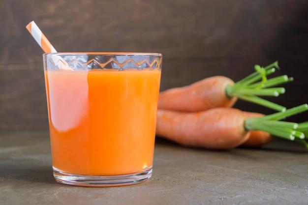 Suco de cenouras maduras frescas em um fundo marrom.