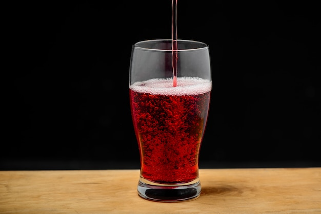 Suco de cereja derramando em vidro na mesa de madeira