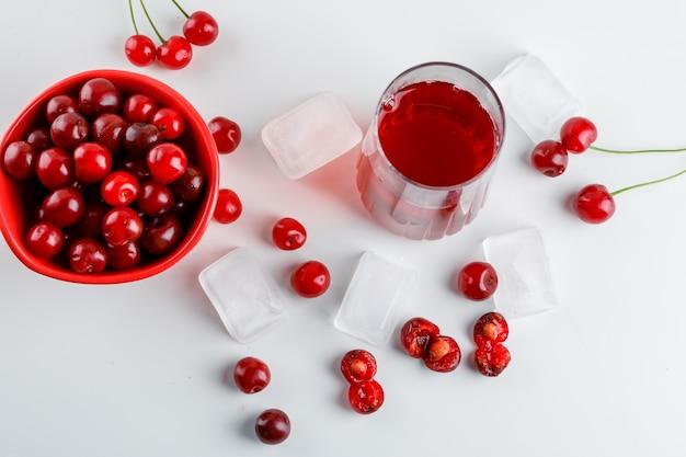 Suco de cereja em um copo com cerejas, cubos de gelo branco