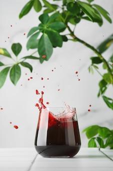 Suco de cereja em vidro. respingo de suco. suco no conceito de verão de mesa de azulejos.