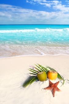 Suco de coquetéis de coco e estrela do mar na praia tropical