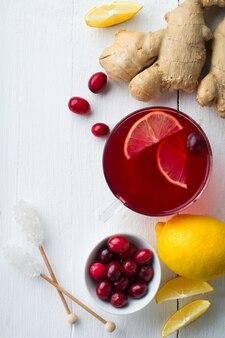 Suco de cranberry fresco com limão, amora, gengibre e açúcar em uma superfície clara. vista do topo. espaço para texto. foco seletivo.