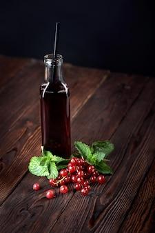 Suco de cranberry orgânico em garrafas com bagas em fundo de madeira