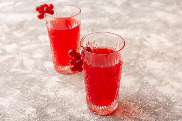 Suco de cranberry vermelho de vista frontal dentro de copos na mesa iluminada