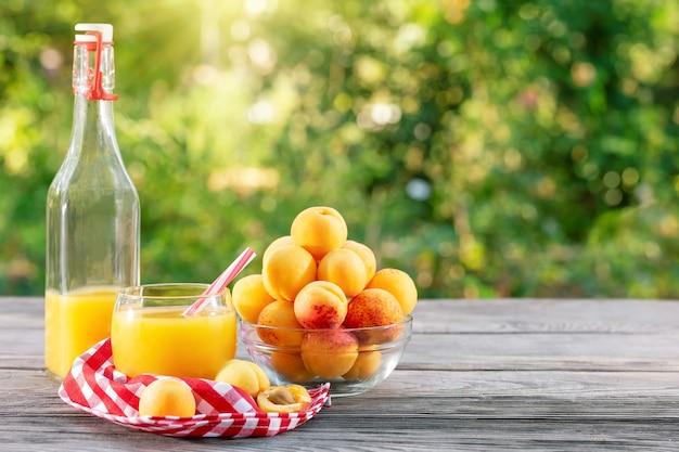 Suco de damasco na garrafa e copo e damascos na mesa de madeira