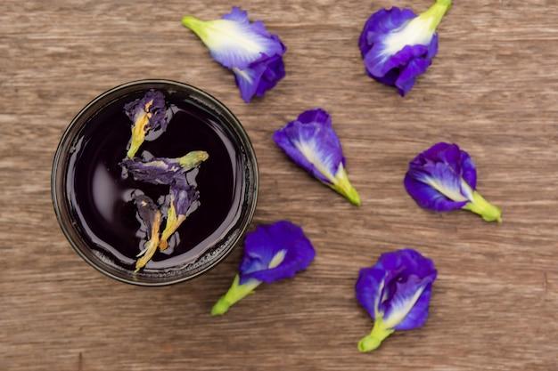 Suco de ervilha borboleta e flor de ervilha borboleta em madeira
