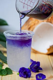 Suco de ervilha com coco na superfície de madeira