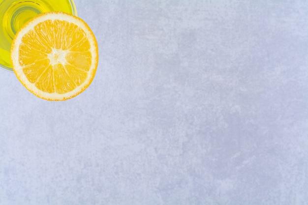 Suco de fruta e uma fatia de laranja na mesa de mármore.