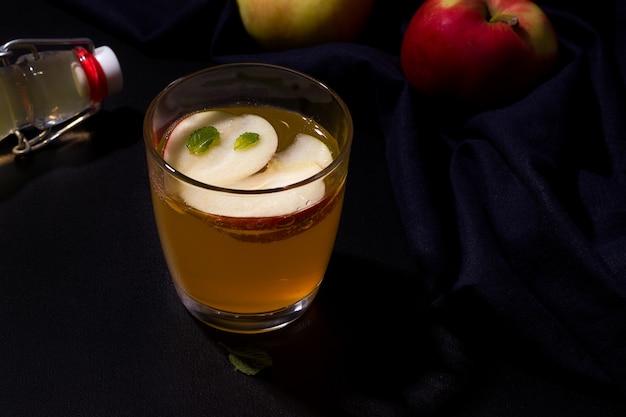 Suco de fruta fermentado feito de maçãs ao lado de ingredientes