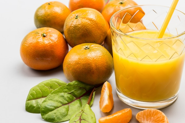 Suco de frutas cítricas em copos. fatias de tangerina com folhas na mesa. fechar-se