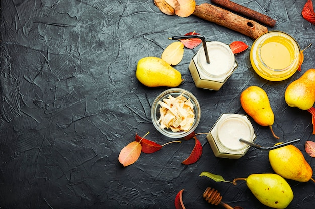 Suco de frutas de outono. smoothie de pera e gengibre e folhas caídas. copie o espaço