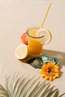Suco de frutas e pedaços de limão algumas flores coloridas e um conceito de verão e férias com folhas de coqueiro