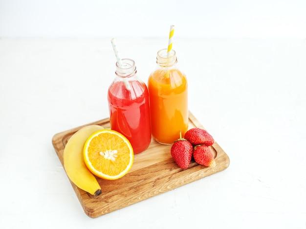 Suco de frutas em garrafas. banana, laranja e morangos. verão e festa.