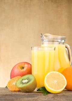 Suco de frutas frescas em copo e fatias em fundo de madeira