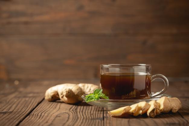 Suco de gengibre quente e gengibre fatiado na mesa de madeira.