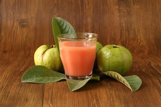 Suco de goiaba vermelha é servido em um fundo de madeira com fatias de goiaba e enfeites de folhas