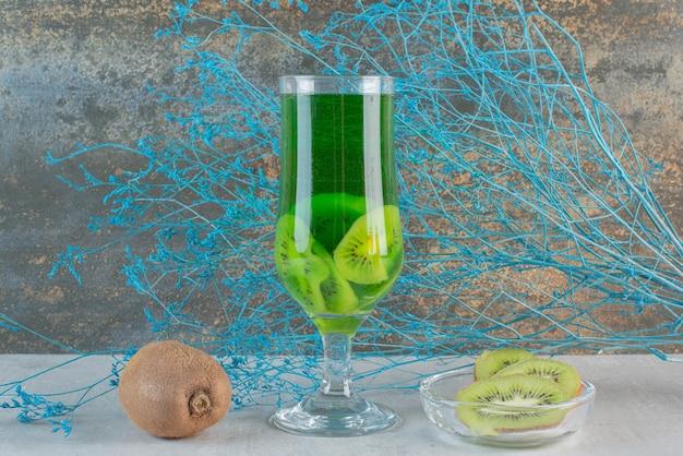 Suco de kiwi com kiwi inteiro e flor murcha. foto de alta qualidade