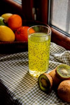 Suco de kiwi com kiwis e outras frutas na superfície do pano