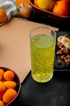 Suco de kiwi com kumquats e outras frutas na superfície preta com espaço de cópia